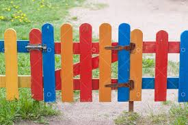 Multi-<b>colored</b> fence <b>strips</b> and wickets at the entrance to garden Image
