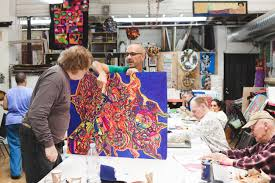 how one bay area studio is creating careers for artists ce assistant studio manager and visual arts instructor eric larson holding up artist dan michiel s mixed media work photo credit nina menconi