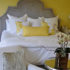 yellow and gray bedroom: yellow and gray bedroom with yellow walls framing gray velvet tufted headboard