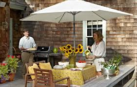 shade deck patio woman standing on a bright patio behind a shingled house pouring from