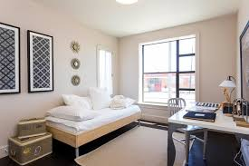 59th street example of a minimalist home office design in other with beige walls dark hardwood bed in office