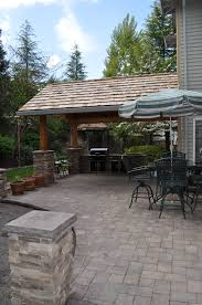 stone patio installation: attached roof with paver patio and cultured stone columns