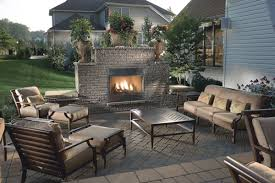 outdoor fireplace paver patio: this simple block fireplace with seat walls and low voltage lighting surrounds a paver patio