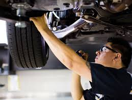 alderson lexus lexus dealership lubbock serving male service tech examining the wheel and brakes of a lexus a flashlight