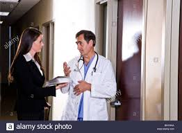 doctor talking pharmaceutical s rep in office corridor doctor talking pharmaceutical s rep in office corridor stock photo