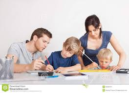 Parents Helping Children With Homework In Kitchen Stock Photos     Parents helping their children with homework Stock Image