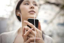 strategies for how to improve english listening skills woman listening to music outside by smart phone   michael h digital vision getty