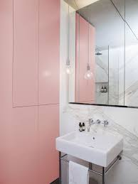dwell bathroom cabinet: a tiny bathroom with pink cabinets and a marble wall
