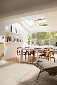 bright scandinavian living room with roof windows and increased natural light wishbone chairs and garden bright special lighting sa
