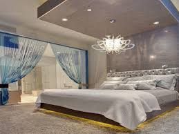 elegant recessed lighting on wooden ceiling design with beautiful chandelier above low king size bed features captivating wall ceiling wall lights bedroom