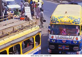 brightly colored buses make their way through the crowded streets while vendors sell their wares brightly colored offices central st
