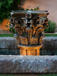resembling a corinthian capital this ornately carved stone water fountain is lit from below backyard landscape lighting