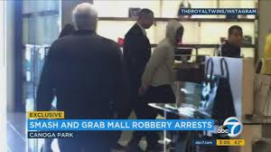 mall com a suspect is taken away by security at neiman marcus after a smash and