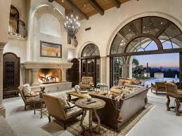 massive two story living room stands an immense marble fireplace below a soaring exposed beam beautiful living room pillar