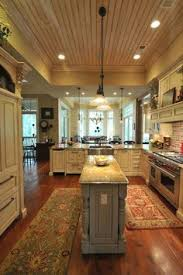 southern coastal homes with a bigger center island though ceiling dining dishwasher drawers stove floor and lighting i like the lighting center island lighting