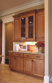 kitchen cabinet door trim: maple raised panel wall cabinets with glass doors and stepped light rail and crown molding