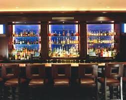 integrated ceiling and bar lighting as well as wall sconces create a cozy club vibe inside the library back bar lighting