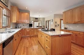kitchen cabinets with granite countertops: this kitchen is awash in natural warm wood tones punctuated with light granite countertops