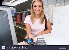 clothes shop assistant store stock photos clothes shop assistant young w handing credit card to shop assistant in clothes shop smiling portrait