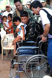 u s department of defense photo essay a philippine national policeman helps a young boy into a wheelchair during a medical outreach event