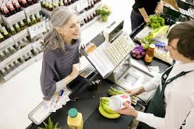 grocery stores that double coupons cashier scanning bananas in grocery store