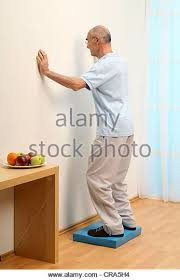 older man from the backside standing to the wall on a instable pad base balanced living room