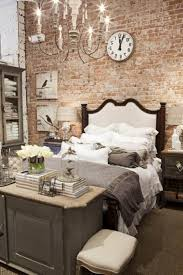 red brick wall with white medium wall clock varnish wooden bed white bed cover white pendant candle lamp white ceramic desk with gray wooden storage white brick desk wall clock