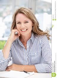 older career w sat at desk smiling royalty stock images older career w sat at desk smiling