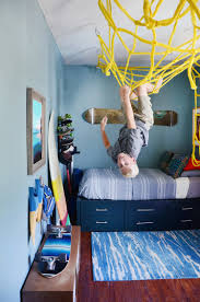 this boys bedroom is bright and full of fun with surfboards and skateboards all over the bright special lighting honor dlm
