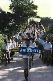 like most things in life peace corps is all about relationships my students walking over the bridge in our village during a ceremony the sign says