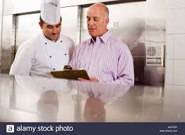 male chef and restaurant manager talking in commercial kitchen male chef and restaurant manager talking in commercial kitchen manager holding clipboard