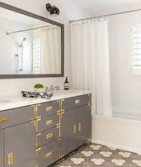 bathroom features gray shaker vanity: bathroom gray bathroom features a gray campaign vanity adorned with brass hardware topped with a white marble countertop fitted with his and hers sinks