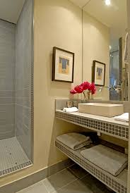 the ample shower room displays a large countertop made of light and dark grey stoneware tileshand wash basin is made of stone ample shower lighting
