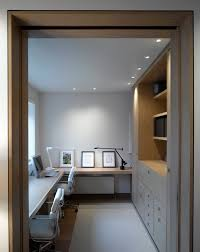 contemporary inspiration for a contemporary home office remodel in london with white walls and medium tone built office furniture