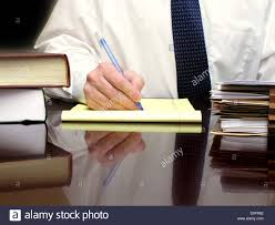 Man sitting at business desk writing on paper with files
