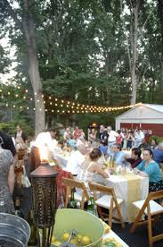 affordable backyard wedding reception in driveway with rented tables cafe lights strung above and backyard wedding ideas