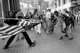 The thrust of xenophobic patriotism aimed directly at an American citizen  The black common man is held back by passerby  Some of those in the background