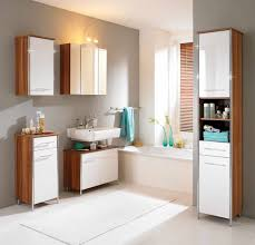 bathroom furniture design of white bathroom cabinet designed with double white doors and white chair also white mantel combine with round glass mirror bathroom furniture design