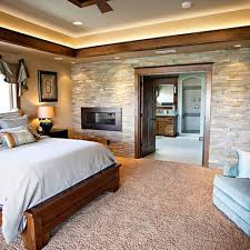 bedroom design by pahlisch homes inclove the stone wall fireplace wood trim and accent lighting near the ceiling needs some more color or a patterned bedroom accent lighting surrounding