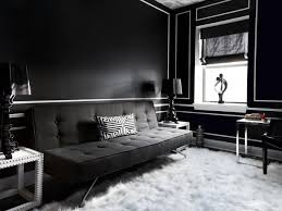danielle colding black and white living room with bold black walls with glossy white trim molding modern black tufted sofa with white black velvet blacks furniture