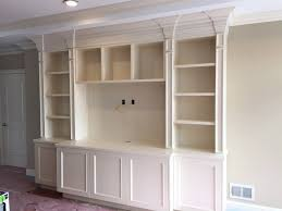 traditional style wall unit with wood carvings pilasters and study desk on the side finished with white paint furniture grade built in study furniture