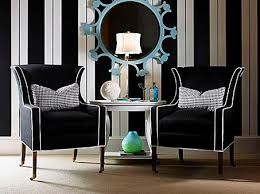 black white turquoise sitting area black curvy wingback chairs with white piping white and black vertical striped walls wallpaper turquoise blue mirror black and white striped furniture