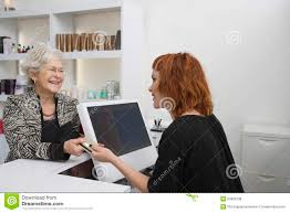 receptionist and client in beauty salon royalty stock image senior w paying for her haircut at reception desk royalty stock photos