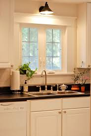 lighting above kitchen cabinets. sconce over the kitchen sink this window has gorgeous trim too lighting above cabinets t