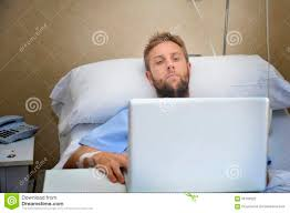 man researching stock photos image  young man in hospital room in bed using internet researching info on his own injury disease