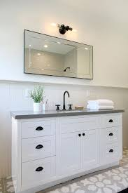 bathroom features gray shaker vanity: white and gray cottage bathroom features a white washstand adorned with bronze cup pulls topped with