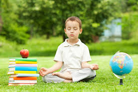 Picture of boy meditating on grass between a stack of books and a globe