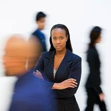 the qualities of a good manager african american businessw standing arms crossed while others walk by