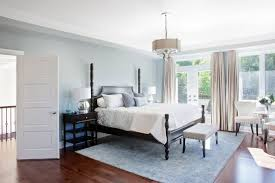 rich hardwood floors are paired with pale blue rug and walls glass doors lead out blacks furniture