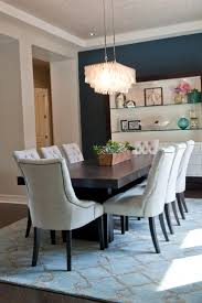 chair dining tables room contemporary: eight off white tufted chairs surround a dark wood table in this chic transitional dining